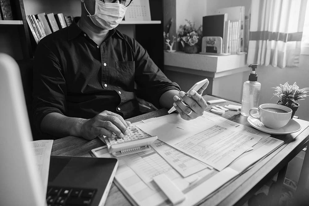 Accountant wearing mask sits behind a desk and is calculating company's annual tax.